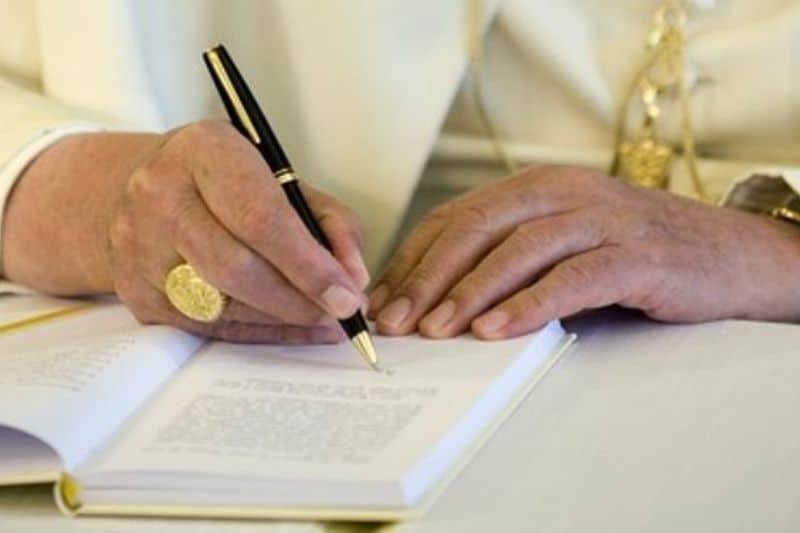 les mains du Pape qui écrit son encyclique