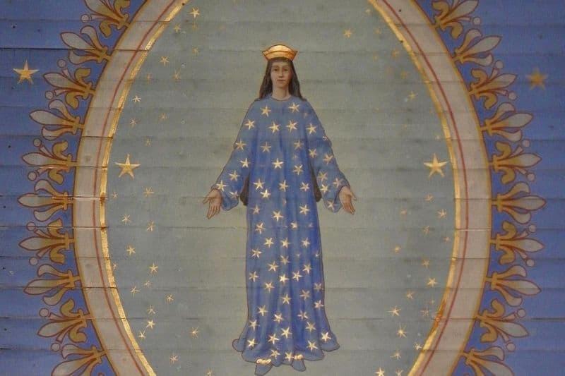 Vierge Marie dans une robe bleue étoilée les mains ouvertes
